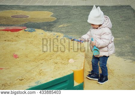 A Little Girl Is Playing In The Sandbox. A Child On The Playground.