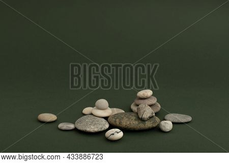 Marble zen stones stacked on green background in health and wellbeing concept