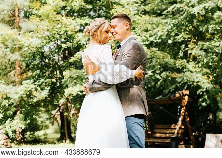 Wedding Day. Happy Young Married Couple Hugs, Newlyweds Caress Each Other Outdoors. Smiling Bride An