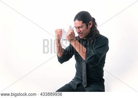 Man On White Background. He Is Tearing Up A Page Because He Got Angry About Something He Read. He Is