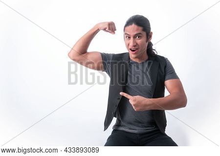 Person With White Background. He Shows In Muscle He Has In His Arm And With The Other Hand He Points