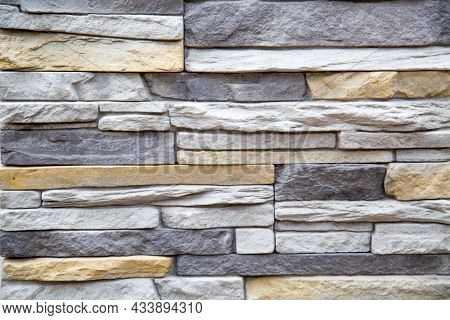 The Background Of The Wall Is Made Of Artificial Stone Of An Elongated Irregular Shape In Gray And W