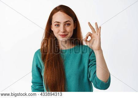 No Problem, Very Well. Smiling Young Woman With Red Long Hair, Look Satisfied, Make Okay Zero Sign,