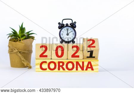 Covid-19 Pandemic In 2022 Symbol. Alarm Clock. Turned A Wooden Cube, Changed Words 'corona 2021' To
