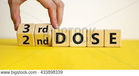 Covid-19 Booster Dose Vaccine Shot Symbol. Doctor Turns Cubes And Changes Words '2nd Dose' To '3rd D