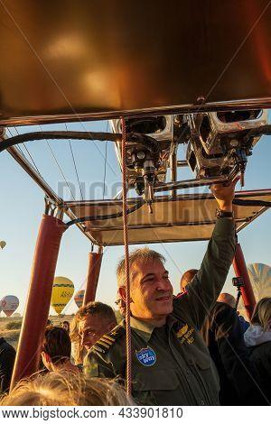 Cappadocia, Turkey - September 14, 2021: A Hot Air Balloon Pilot Navigates His Balloon Through The S