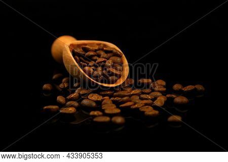 Coffee Beans In A Wooden Scoop Isolated On A Black Background. Roasted Coffee Beans Isolated. A Wood