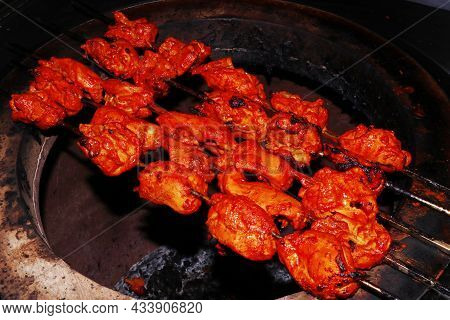 Spice Marinated Chicken Cubes ( Chicken Tikka )skewers Cooking In A Clay Oven Known As Indian Tandoo