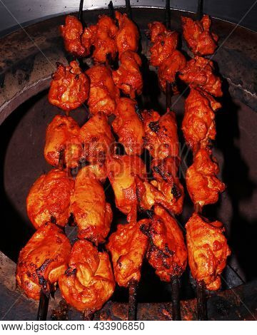 Indian Spice Marinated Chicken Cubes ( Chicken Tikka )skewers Cooking In A Clay Oven Known As Tandoo