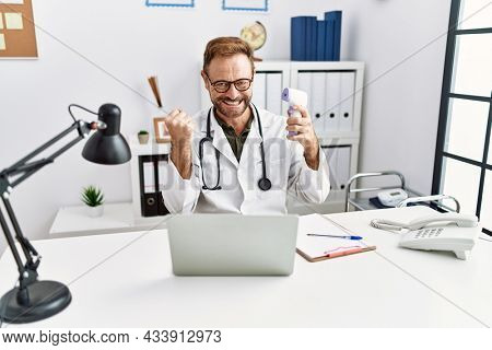 Middle age doctor man holding thermometer at the clinic screaming proud, celebrating victory and success very excited with raised arms