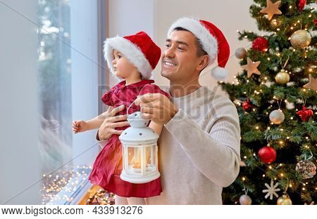 winter holidays and family concept - happy middle-aged father with lantern and baby daughter looking through window over christmas tree at home