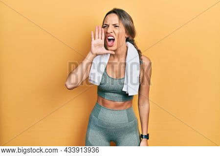 Beautiful hispanic woman wearing sportswear and towel shouting and screaming loud to side with hand on mouth. communication concept.
