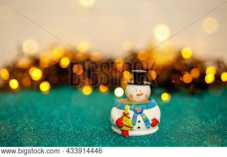 Snowman With Bokeh Christmas Lights In The Background. Christmas Card Decorated With Bokeh And Light