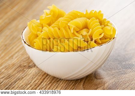 White Glass Bowl With Raw Pasta Fusilli On Wooden Table