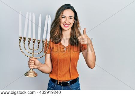 Young hispanic girl holding menorah hanukkah jewish candle smiling happy and positive, thumb up doing excellent and approval sign