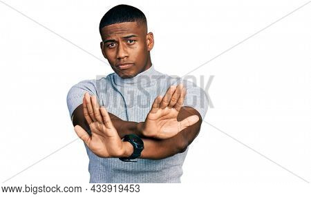 Young black man wearing casual t shirt rejection expression crossing arms doing negative sign, angry face