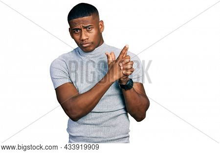 Young black man wearing casual t shirt holding symbolic gun with hand gesture, playing killing shooting weapons, angry face