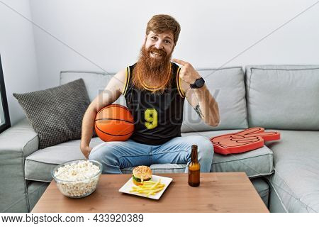 Caucasian man with long beard holding basketball ball cheering tv game smiling cheerful showing and pointing with fingers teeth and mouth. dental health concept.