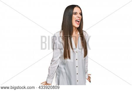 Young beautiful woman wearing casual white shirt angry and mad screaming frustrated and furious, shouting with anger. rage and aggressive concept.