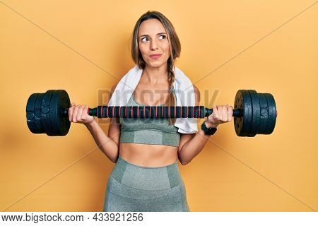 Beautiful hispanic woman wearing sportswear using dumbbells smiling looking to the side and staring away thinking.