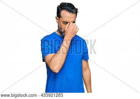 Middle aged man with beard wearing casual blue t shirt tired rubbing nose and eyes feeling fatigue and headache. stress and frustration concept.