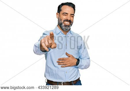 Middle aged man with beard wearing business shirt laughing at you, pointing finger to the camera with hand over body, shame expression