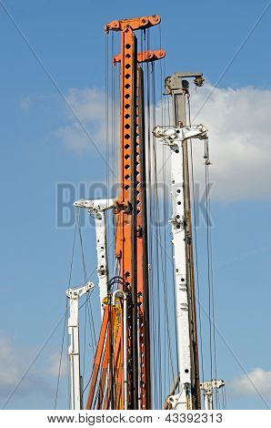 Vertical cranes agains blue sky