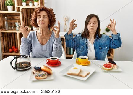 Family of mother and down syndrome daughter sitting at home eating breakfast relax and smiling with eyes closed doing meditation gesture with fingers. yoga concept.