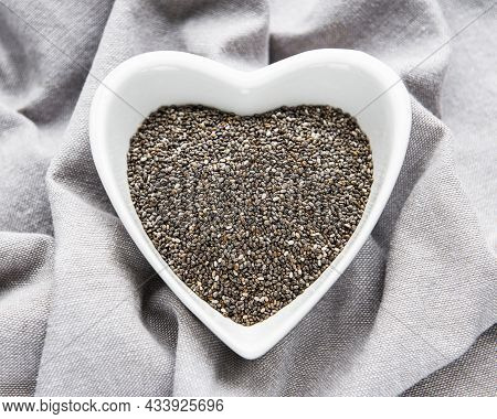 Chia Seeds In White Bowl  On Grey Textile Background.