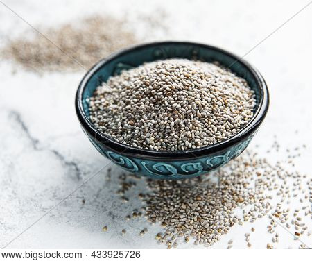 Chia Seeds In Bowl On White Marble Background.