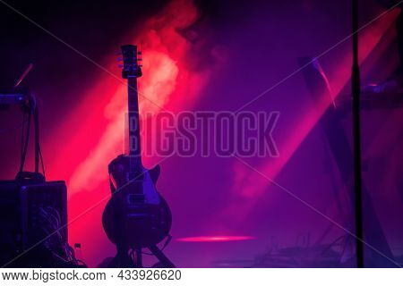 Acoustic guitar on the stage under beam of light with smoke with copy space. Music, summer festival concept.