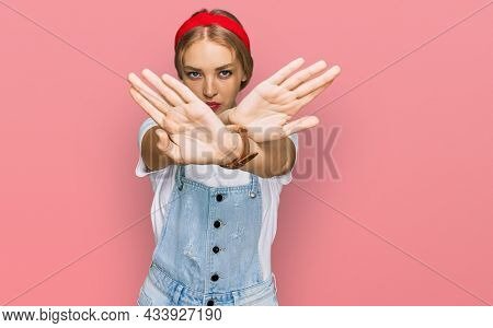 Young caucasian girl wearing casual clothes rejection expression crossing arms and palms doing negative sign, angry face