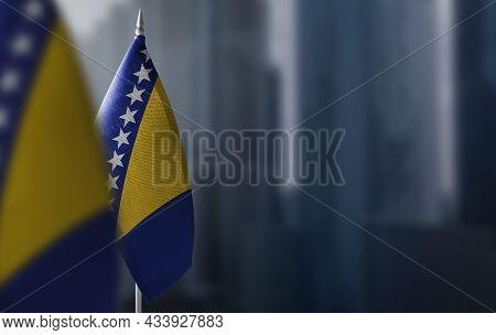 Small Flags Of Bosnia And Herzegovina On A Blurry Background Of The City