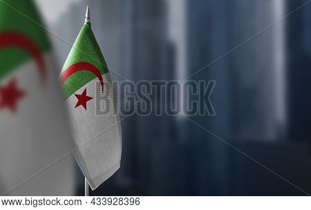 Small Flags Of Algeria On A Blurry Background Of The City