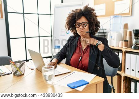 African american woman with afro hair working at the office wearing operator headset cutting throat with hand as knife, threaten aggression with furious violence