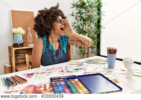Beautiful african american woman with afro hair painting at art studio shouting and screaming loud to side with hand on mouth. communication concept.