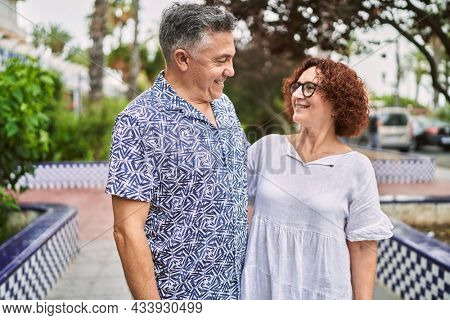 Middle age hispanic couple together outdoors on summer day
