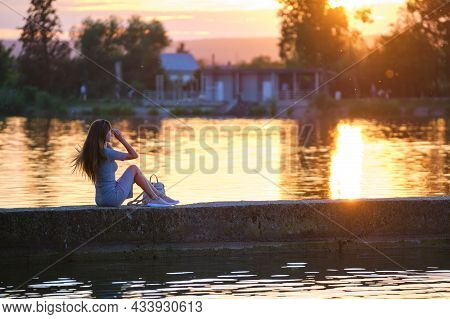 Side View Of Lonely Woman Sitting Alone On Lake Shore On Warm Evening. Solitude And Relaxing In Natu