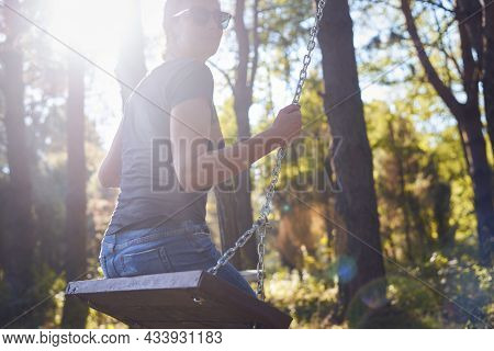 Woman in nature in sunset. People in nature.Woman relaxing on swing in nature in sunset. people. Happy people nature. Happy woman on swing in nature sunset in nature. Woman on swing in forest nature sunset. Woman. People. Sunset. Nature.