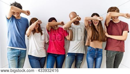 Group of young friends standing together over isolated background smiling cheerful playing peek a boo with hands showing face. surprised and exited
