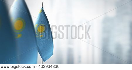 Small Flags Of Kazakhstan On A Blurry Background Of The City