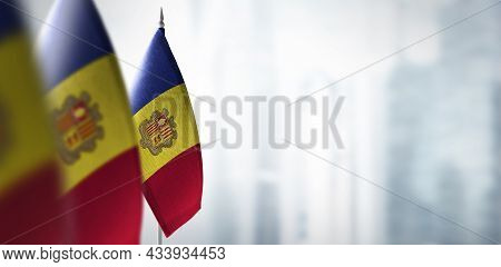 Small Flags Of Andorra On A Blurry Background Of The City