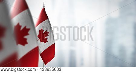 Small Flags Of Canada On A Blurry Background Of The City
