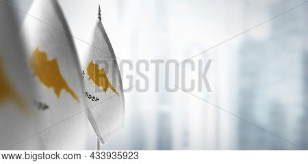 Small Flags Of Cyprus On A Blurry Background Of The City