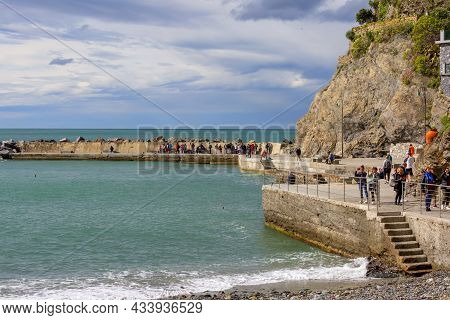 Monterosso, Cinque Terre - Italy, May 12, 2019: View On Seaside, People On The Stone Pier, Riviera D