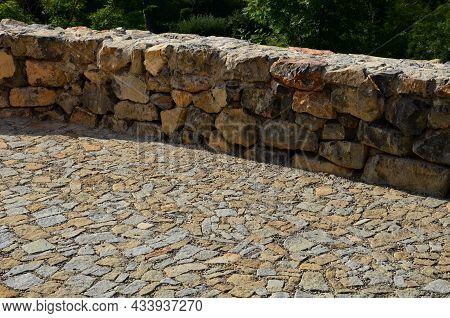 Beautifully Folded Retaining Wall Of Rough Stone Joined With Cement Mortar. Brown Beige Yellow Irreg
