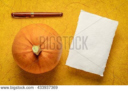 small sheet of blank white Khadi rag paper against dark yellow gampi paper, with a pumpkin and a stylish pen, fall holidays theme
