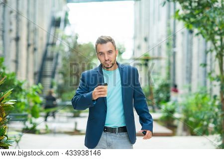 A young successful businessman is working outdoor using smartphone. Man in a casual wear. Business, freelance and remote work.