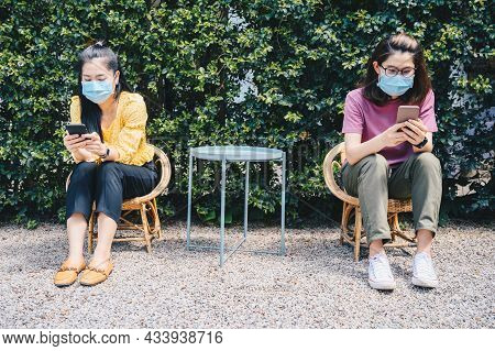 Women Wearing Face Mask While Sitting Outdoor, Keep Space For Avoid Spreading Of Virus Disease In Co