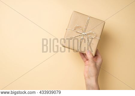 First Person Top View Photo Of Hand Holding Craft Paper Giftbox With Twine Bow On Isolated Beige Bac